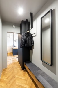 Mirror and clothes on rack in grey anteroom interior with light