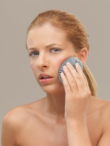 portrait woman using metal dish scrubber face